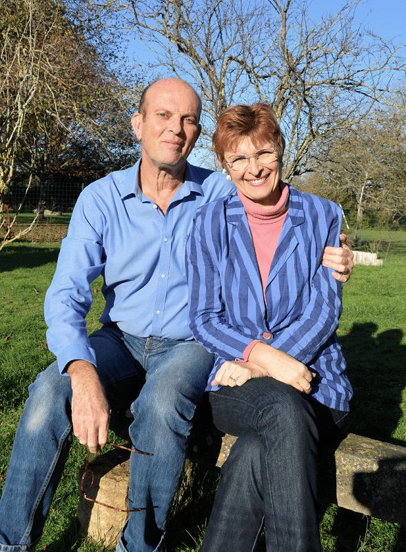 Yveline et Bruno assis dans le jardin du gîte Les Hortensias à Baugy